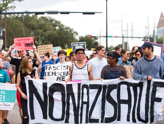 Anti-white nationalist protesters march outside of