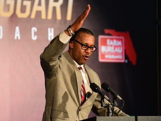 """Florida State's new head coach Willie Taggart does """"the chop"""" during a press conference at Doak Campbell Stadium."""
