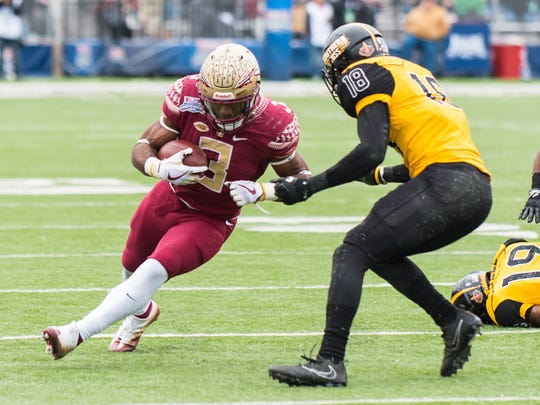 Florida State freshman running back Cam Akers (3) to brush past Southern Mississippi senior defensive back Tarvarius Moore (18) defensive back Kelsey Douglas (6) during the third quarter at the Independence Bowl.