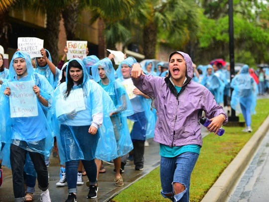 Members of PeaceJam march towards The Globe on a rainy