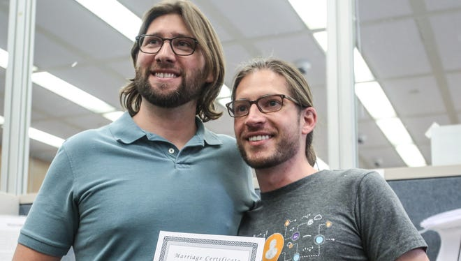 Craig Bowen (left) and Jake Miller (right) hold their certificate of marriage, becoming the first gay couple married by Marion County, Indiana, Clerk Beth White at the City-County Building in Indianapolis.
