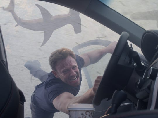 Ian Ziering and an airborne hammerhead in a scene from