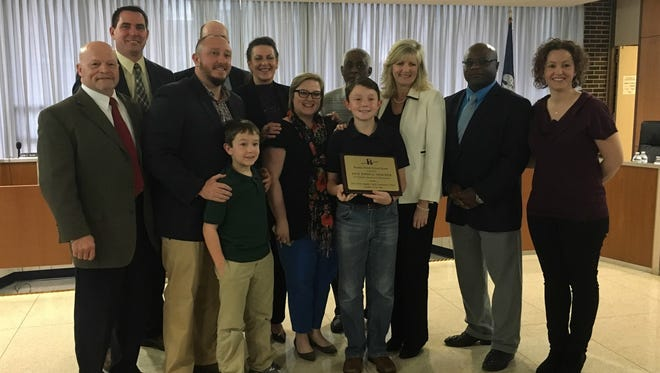 Peabody Montessori Elementary fifth-grader Jack Thacker (center) stands with family members and officials with his school and district as he is recognized Tuesday as the district Student of the Year for the elementary category.