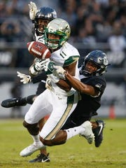 UCF Knights defensive back Mike Hughes (right) knocks