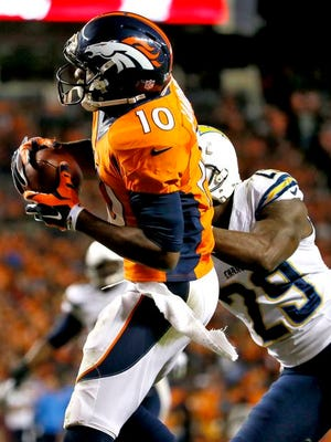 Denver Broncos wide receiver Emmanuel Sanders (10) scores his third touchdown of the NFL football game, as San Diego Chargers cornerback Shareece Wright (29) defends during the second half Thursday, Oct. 23, 2014, in Denver.