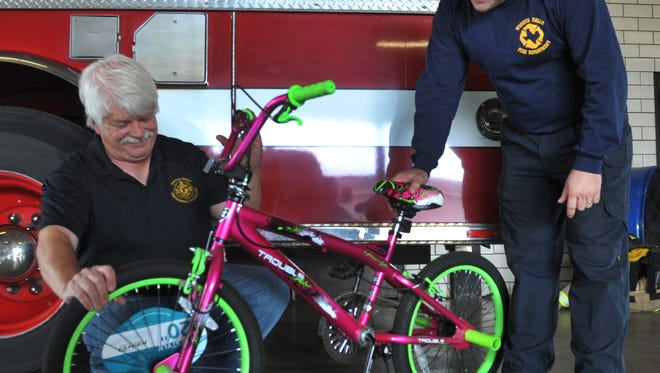 Members of the Wichita Falls Fire Department examine one of the hundreds of bicycles WFFD gives away annual in the Operation Santa Claus project.