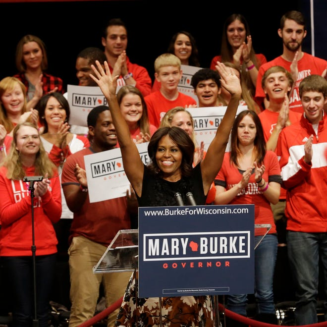 First lady Michelle Obama acknowledges the crowd at a campaign event for Wisconsin Democratic gubernatorial candidate Mary Burke, Tuesday, in Madison. Mrs. Obama rallied young voters in Wisconsin's race for governor, saying if they show up to vote Republican Gov. Scott Walker can be defeated.