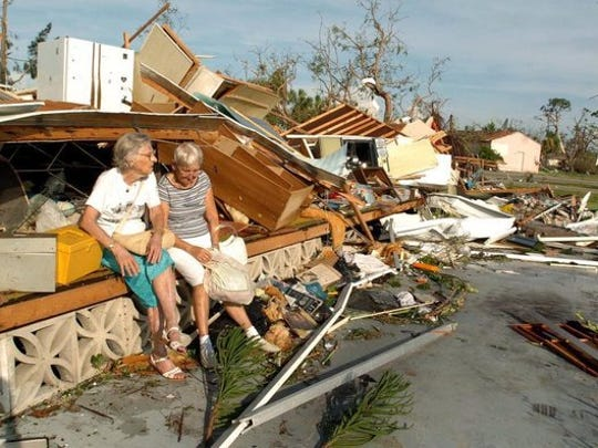 Anne M. Loehnert, left, sits on what was her home with her friend, Jane McCallum at Wind Mill Village in Punta Gorda, Fla., Saturday, Aug. 14, 2004, as she and other residents deal with the devastation of Hurricane Charley.