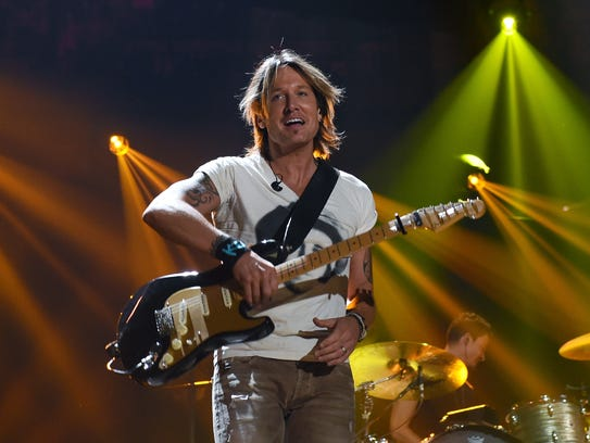 Keith Urban takes off his guitar as he performs during