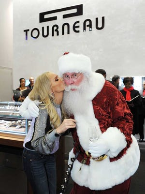 Singer and actress Kristin Chenoweth gives a kiss to Santa Claus, known as Santa Tom Z., at the 2012 Tourneau Mistletoe Event in New York.