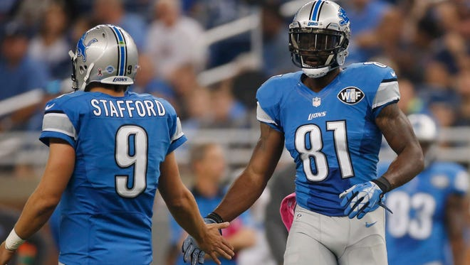 Calvin Johnson #81 celebrities breaking the franchise record of the most catches with Matthew Stafford #9 of the Detroit Lions while playing the Arizona Cardinals at Ford Field on October 11, 2015 in Detroit, Michigan.