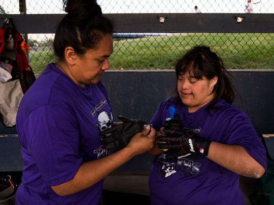 Norma Rodriguez, left, helps her daughter Kristi strap on her batting gloves before taking the plate at a Fort Collins Unified softball game against the Sliders on Monday, June 12, 2018, at Rolland Moore Park in Fort Collins, Colo.