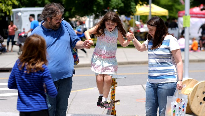 Lyra Bales, 6, walks a tight rope with the aid of her father, Christopher and mother Kelly, during the Children's Festival of Reading at the World's Fair Park, on Saturday, May 21, 2016.