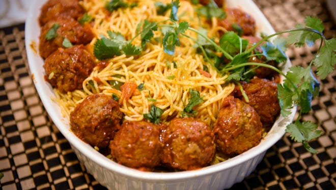 Noodles and meatballs are prepared by African Yen catering company Thursday, June 2, in the kitchen of New York Gyro in St. Cloud.