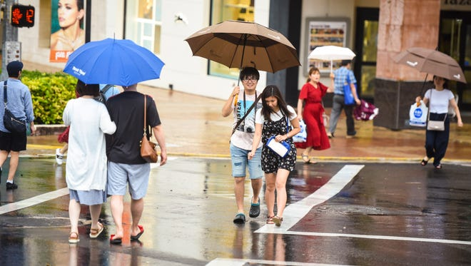 Pedestrians use umbrellas as shelter from the rain as they go about in Tumon on Friday, July 6, 2018.
