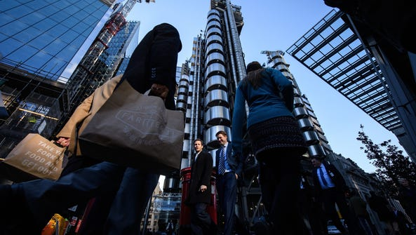 Workers walk past the Lloyd's building in the financial