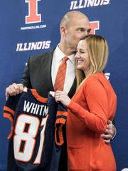 Josh Whitman, gives his wife, Hope, a kiss as he is announced as the new Illinois athletic director during a news conference at Bielfeldt Athletic Administration Building in Champaign, Ill., Thursday, Feb. 18, 2016. The 37-year-old former Illinois and NFL player was most recently the athletic director at Washington University in St. Louis. (Heather Coit/The News-Gazette via AP) MANDATORY CREDIT