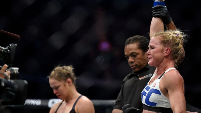 Holly Holm, right, celebrates after defeating Ronda Rousey, left, during their UFC 193 Bantamweight title fight in Melbourne, Australia.