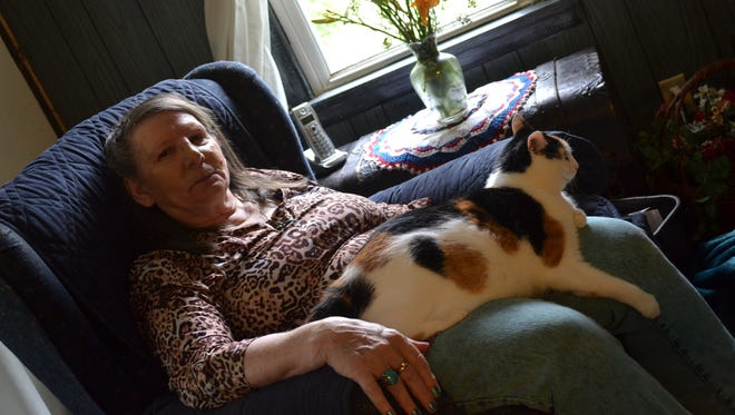 Louise Sprenger holds her cat, Harley, in their Rocky Ridge home. Harley receives free food through the Meals on Wheels Loves Pets program, which helps homebound seniors keep their pets.
