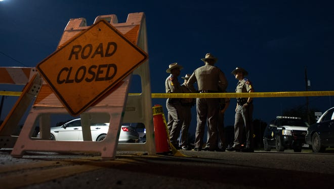 Texas state troopers stand in front of the closed road leading to First Baptist Church in Sutherland Springs the day after a shooting that left 26 dead, Nov. 6, 2017.