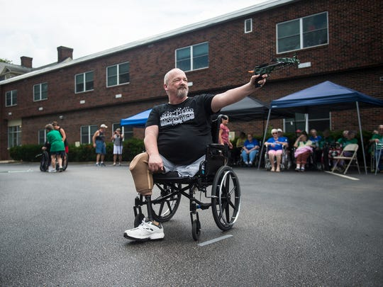 Resident Randy Altland aims for the bull's-eye during the dart competition at the Hanover Hall Summer Olympics on Wednesday in Hanover.