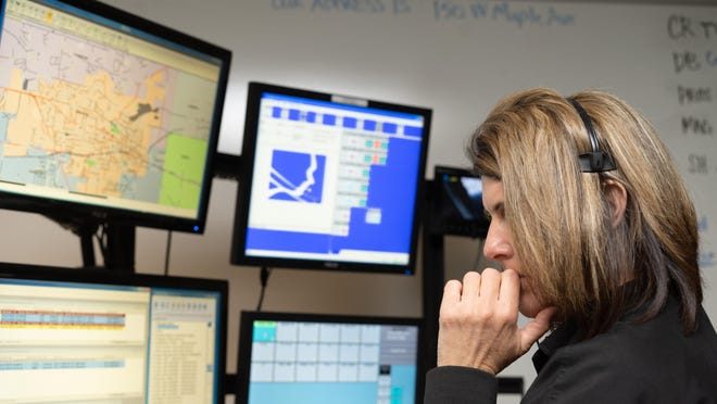 Lenawee County dispatcher Nicole Keefer takes a 911 call April 11, 2019, at her work station in central dispatch.