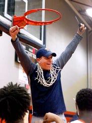 Blackman head coach Barry Wortman cuts down the the