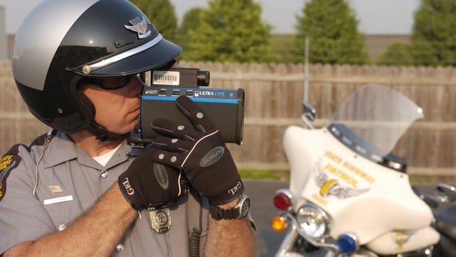 A state trooper checks the calibration on his laser speed detecting device before going out on patrol.