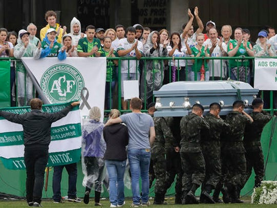 Military carry a coffin with the remains of Chapecoense soccer team member, victim of an air crash in Colombia, during funeral ceremony at the Arena Conda stadium in Chapeco, Brazil, Saturday, Dec. 3, 2016.