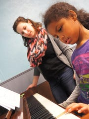 Brooklyn practices the piano with teacher Sarah Beyersdorf