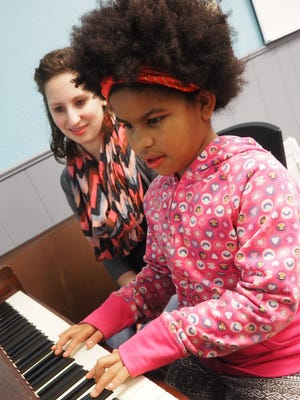 Isabella practices the piano with teacher Sarah Beyersdorf during a free lesson held at Big Brothers Big Sisters as a part of Mary Scharinger's Play it Forward program.