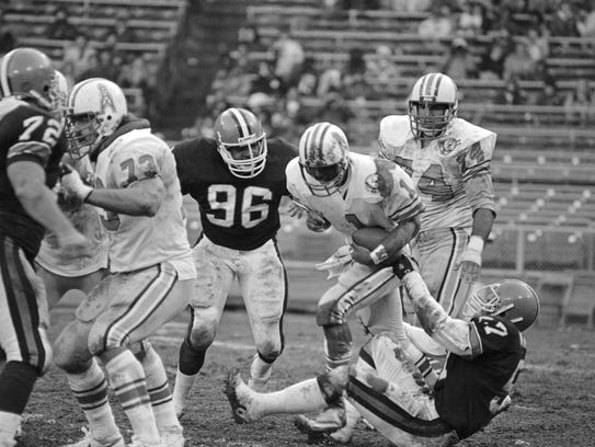 Houston Oilers quarterback Warren Moon (1) is sacked