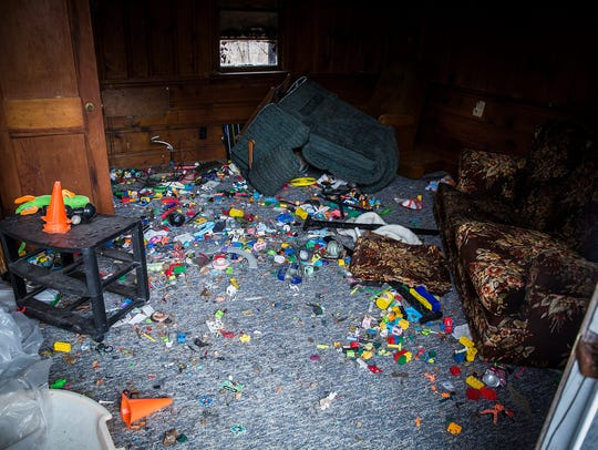 Toys are scattered on the floor of a cabin at the former
