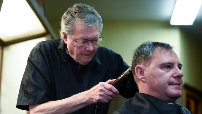 Larry Ramharter cuts the hair of Joe Eining on Ramharter's last day. Ramharter is retiring and selling Southway Barbershop after cutting hair at the location for 53 years.