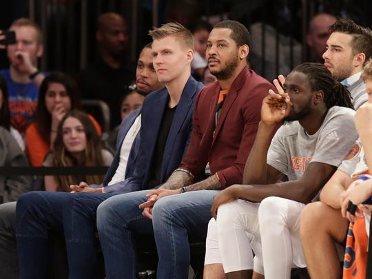 New York Knicks' Carmelo Anthony, center, and Kristaps Porzingis, left, watch from the bench during the second half of the game against the Toronto Raptors on April 9, 2017, in New York.