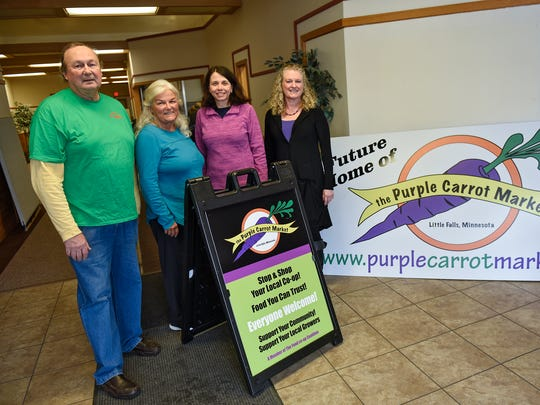 Jim Weiss, Susy Prosapio, Cathy Hartle and Darlene Brand stand near signs advertising the future location of the Purple Carrot Market Friday, March 30, in Little Falls.