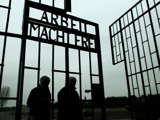 People walk through the gate of the Sachsenhausen Nazi