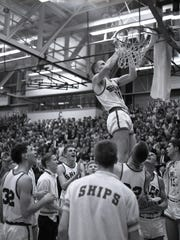 Manitowoc senior Bill Stepnafski cuts down the net following the Ships' sectional championship at JFK Fieldhouse. Manitowoc would go on to win the WIAA state title in Madison.