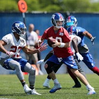 New York quarterback Eli Manning (10) looks up the field as running back Rashad Jennings (23) waits for a handoff during football practice Monday, May 23, 2016 in East Rutherford, N.J. (AP Photo/Mel Evans)