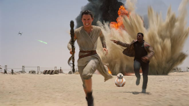 "Disney This photo provided by Disney shows Daisey Ridley as Rey, left, and John Boyega as Finn, in a scene from the upcoming film, ?Star Wars: The Force Awakens.? This photo provided by Disney shows Daisey Ridley as Rey, left, and John Boyega as Finn, in a scene from the new film, ""Star Wars: The Force Awakens."""