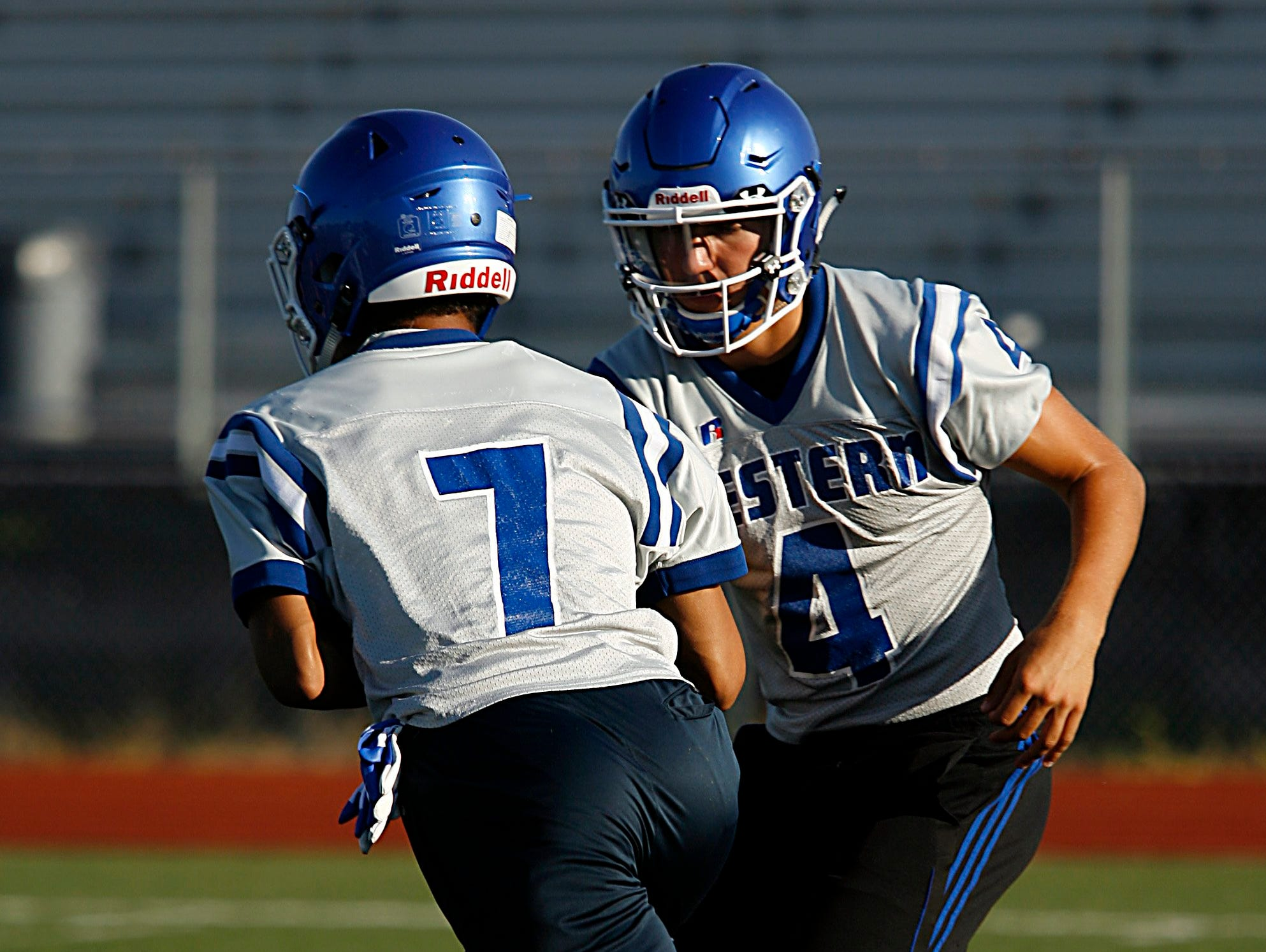 Walled Lake Western QB John Tracy hands off to Cody White during their team's first football practice Monday.