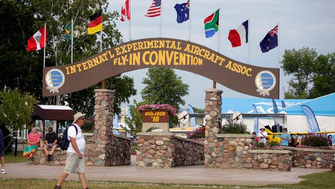A convention-goer passes by the historic Brown Arch on the penultimate day of EAA AirVenture Oshkosh 2016  at Wittman Regional Airport in Oshkosh.