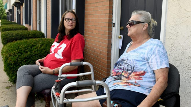 Kathryn Gower, 71, (right) sits with Heather Cutlip outside the Magnuson Hotel in Jackson Township.  Gower is living at the extended stay hotel temporarily because she and her two adult sons were evicted last month from a rental house in Canton.