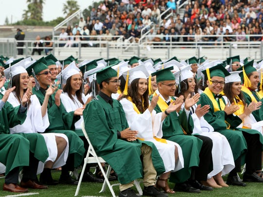Members of the 50th class to graduate from Alisal High School applaud their classmates during the graduation ceremony on Thursday