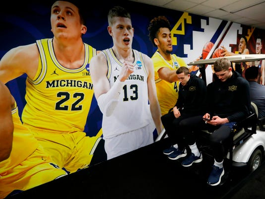 Michigan's Duncan Robinson, left, and Moritz Wagner ride on a cart on their way to a news conference for the championship game of the Final Four NCAA college basketball tournament, Sunday, April 1, 2018, in San Antonio. (AP Photo/Charlie Neibergall)