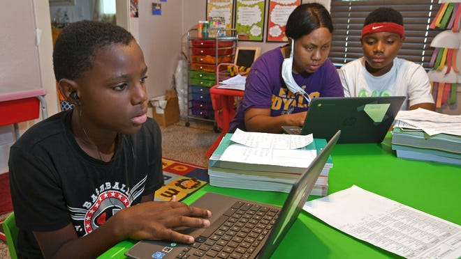 From left: Micheal Henry, 11; his mother Mary Euell, 30; and his brother Mario Henry, 12, work through math lessons remotely at their west Erie home Tuesday on the first day of classes for the Erie School District. Most of the district's 11,000 students are beginning the school year with remote learning to slow the spread of COVID-19.