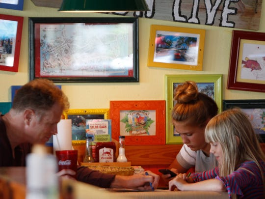 Tim Dieseling, left, plays tic-tac-toe with daughter, Claire while daughter, Ellie studies the screen on her phone at Pincher's Crab Shack in the Gulf Coast Town Center in Fort Myers Wednesday.