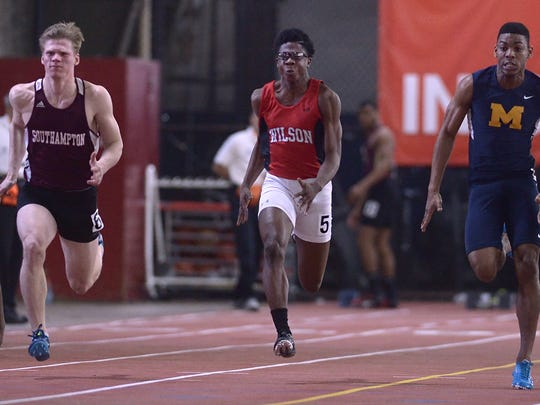 Wilson Magnet's Kelly Brown, center, runs a trials heat of the 55 meter dash during the 2015 state championships at Cornell University's Barton Hall.