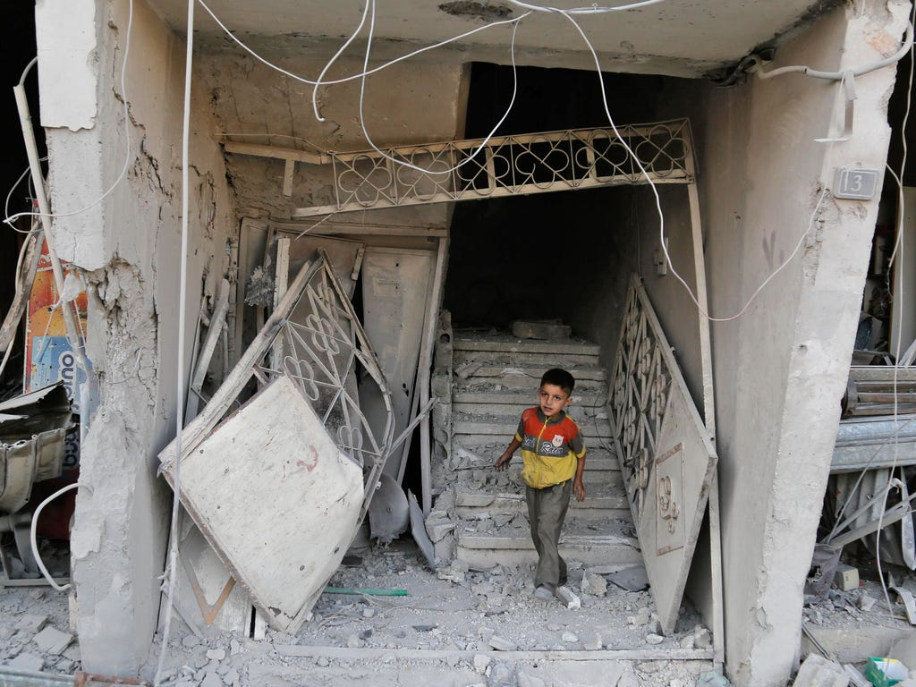 A Syrian child walks out of a damaged building on July 25, 2017, following an air strike late the previous night on the rebel-held town of Arbin, east of the capital. \u000dWomen and children were among the dead in the 11:30 pm  strike on Arbin in th