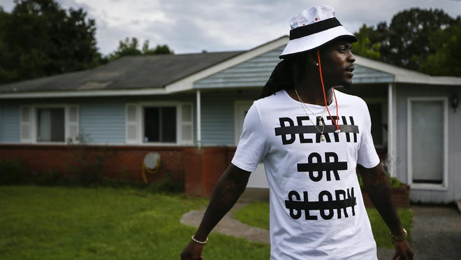 Cincinnati Bengals fourth-year cornerback Dre Kirkpatrick, 25, stands in front of his childhood home as he describes growing up in the troubled Oakleigh Estates neighborhood of Gadsden, Alabama, on Friday, June 12, 2015. Kirkpatrick recalled pick-up games of basketball in a neighbor's yard that eventually had to stop after a drive-by shooting injured three of the players.